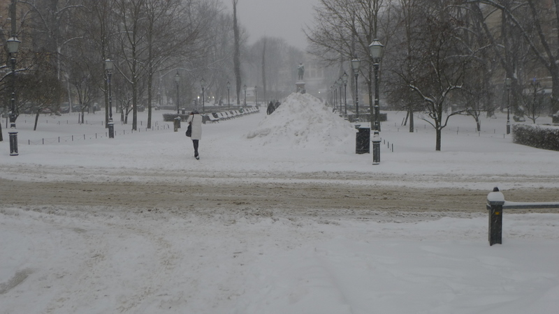 Woman walking away, Esplanade, formal park in Helsinki, in winter. Lots of snow.