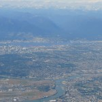 aerial view of Vancouver with blue mountains in the background and Fraser River in front centre